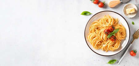 Italian spaghetti with cherry tomatoes in a white plate on a light background, top view, banner, copy space Reklamní fotografie - 153948765