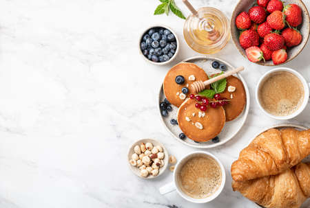 breakfast top view, pancakes, croissants, berries, nuts and coffee on a white marble background