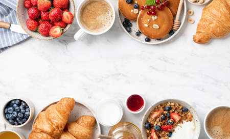 breakfast top view, pancakes, croissants, granola with yogurt, berries, nuts and coffee on a white marble background Reklamní fotografie - 153949819