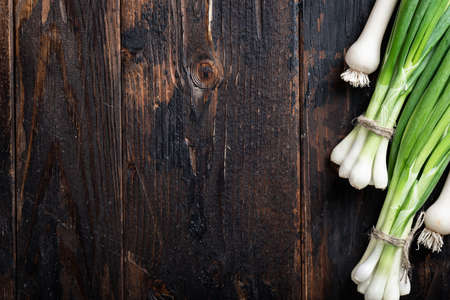 fresh green onions and garlic on a dark wooden background, place for text Reklamní fotografie