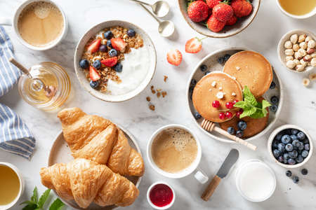 Breakfast table with granola, fresh berries, croissants, pancakes, honey, nuts and coffee on a marble background