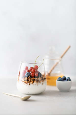 Breakfast, granola with yogurt and berries in a jar on a light background
