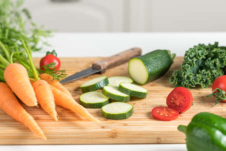 Healthy food concept. Fresh vegetables on a white table on a cutting board in the kitchen. Selective focus