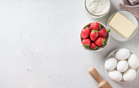 Ingredients for cooking strawberry pie on white background, top view, place for text. Strawberry, eggs, flour, butter.