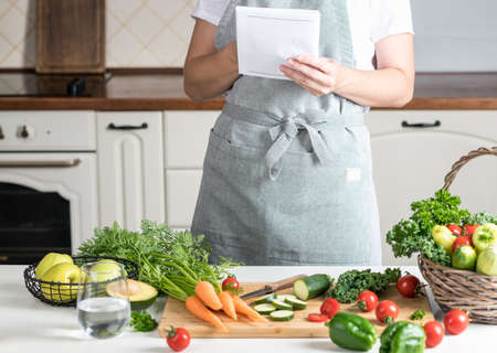 woman cooking in the kitchen. fresh healthy vegetables on a cutting board Reklamní fotografie - 154001270