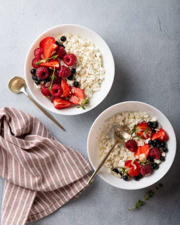 cottage cheese bowl with raspberries, strawberrieson a light background, top view