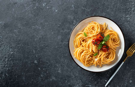 Pasta with cherry tomatoes in a white plate on  dark