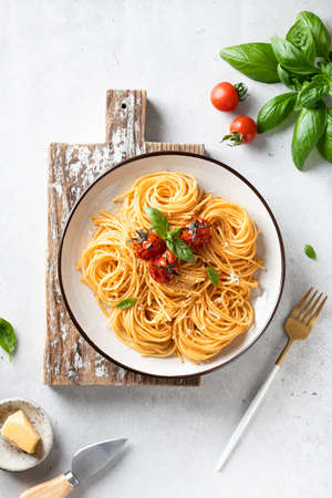 pasta with cherry tomatoes in a white plate on a light background, italian food. Reklamní fotografie - 155420932