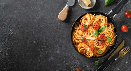 pasta in a black pan on a dark background , italian cuisine. Top view, copy space Reklamní fotografie - 154866363