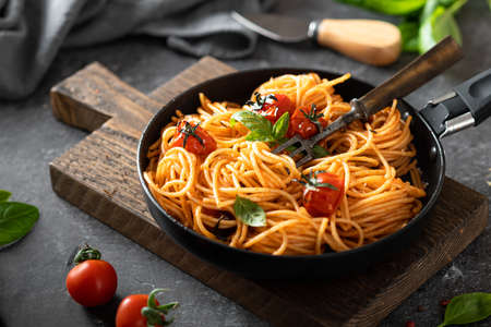 pasta in a black pan on a dark background , italian cuisine, selective focus Reklamní fotografie