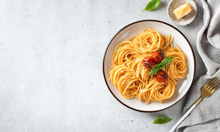 Italian spaghetti with cherry tomatoes in a white plate on a light background, top view, copy space Reklamní fotografie - 154865430