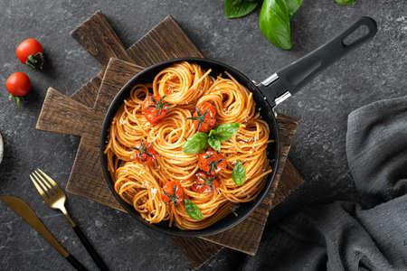 pasta in a black pan on a dark background , italian cuisine. Top view, copy space Reklamní fotografie - 154865575