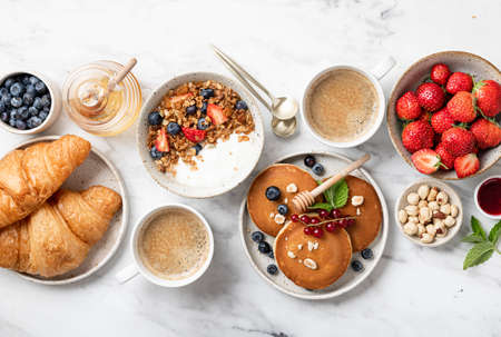 breakfast top view, pancakes, croissants, granola with yogurt, berries, nuts and coffee on a white marble background Reklamní fotografie - 154951580