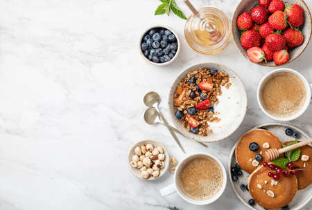 breakfast top view, pancakes, croissants, granola with yogurt, berries, nuts and coffee on a white marble background, copy space Reklamní fotografie - 154951966