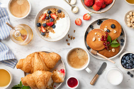 breakfast top view, pancakes, croissants, granola with yogurt, berries, nuts and coffee on a white marble background Reklamní fotografie - 154951801