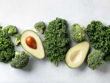Avocado, kale and broccoli, detox dieting concept. Green vegetables on a white background, top view Reklamní fotografie - 154956021