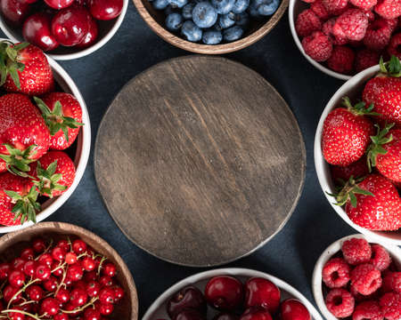 Berries frame with strawberries, raspberries, blueberries, cherries, currants on dark stone background. Flat lay, top view, place for text Reklamní fotografie - 155049256
