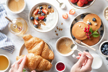 breakfast with croissants, granola with yogurt, pancakes, fresh berries, honey, nuts and coffee on a white marble background
