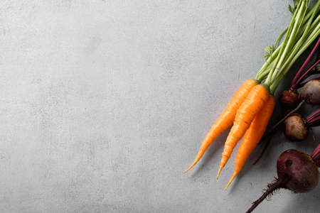 organic carrots and beets with leaves on light background, top view, copy space