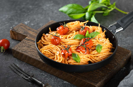 pasta in a black pan on a dark background , italian food, selective focus Reklamní fotografie