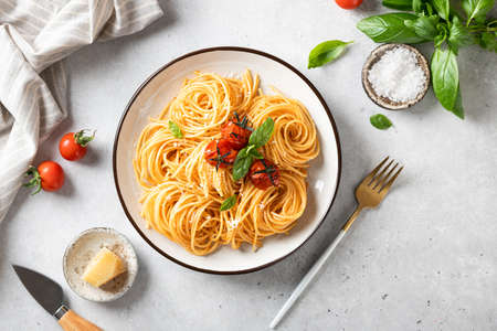 pasta with cherry tomatoes in a white plate on a light background, italian food. Reklamní fotografie - 155407989
