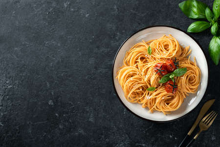 spaghetti in a white plate on a dark background, italian cuisine. Top view, copy space