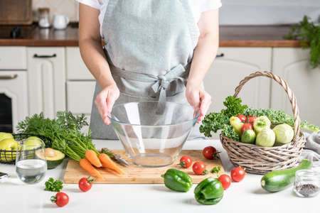 woman cooking in the kitchen. fresh healthy vegetables on a cutting board Reklamní fotografie - 155409605