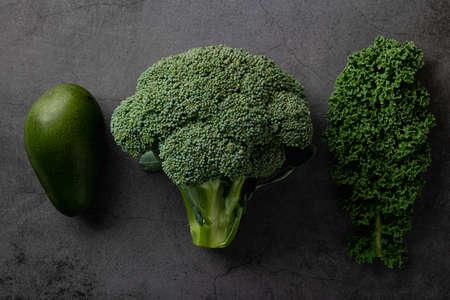 Avocado, kale and broccoli, detox dieting concept. Green vegetables on a dark stone background, top view Reklamní fotografie