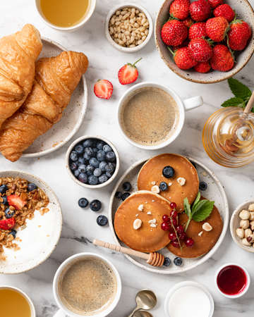 breakfast top view, pancakes, croissants, granola with yogurt, berries, nuts and coffee on a white marble background Reklamní fotografie - 155703560