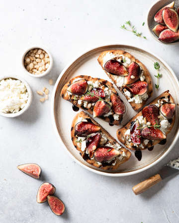 bruschetta with figs, cream cheese, balsamic sauce and pine nuts in a ceramic plate on a light background, top view Reklamní fotografie