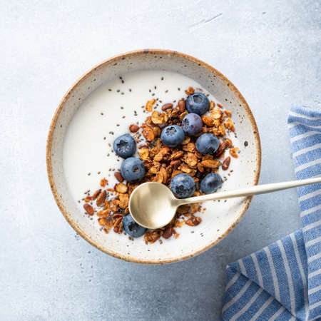 Breakfast, granola with yogurt, blueberries and chia seeds on a light blue background, top view
