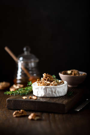 brie cheese with walnuts on a wooden cutting board . Selective focus, dark background