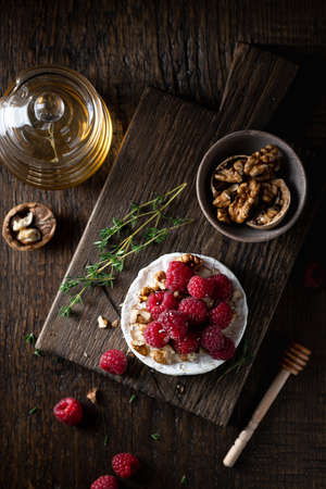 brie or camembert cheese with raspberries, honey and walnuts . Selective focus, dark background, top view