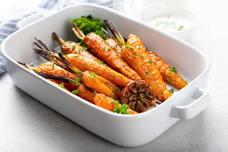 baked carrots in a white ceramic form on a light background, close-up, selective focus