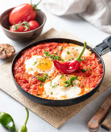 Shakshuka, fried eggs with vegetables in a frying pan, traditional israeli cuisine