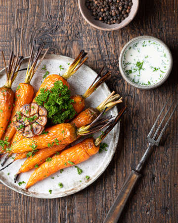 baked carrots on a ceramic plate on a wooden background, view from above.