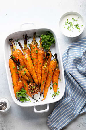 baked carrots in a ceramic form on a light background, top view