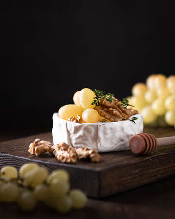 brie cheese with grapes and walnuts on a cutting board on wooden background, selective focus.
