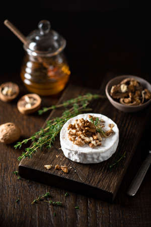 brie or camembert cheese with walnuts and honey on a wooden cutting board . Selective focus, dark background