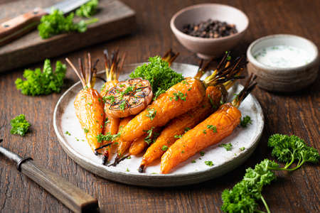 baked carrots on a plate on a wooden table, selective focus