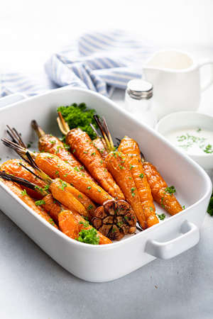 baked carrots in a ceramic form on a light background, close-up, selective focus Reklamní fotografie