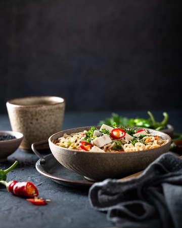Asian noodle soup, ramen with tofu and vegetables in ceramic bowl on dark background, selective focus Reklamní fotografie
