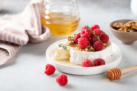 sliced brie cheese with raspberries, honey and walnuts . Selective focus, white background