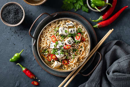 Asian food, ramen with tofu and vegetables in ceramic bowl on dark background, top view