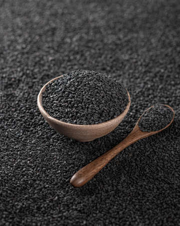 Black sesame seeds in a ceramic bowl, selective focus