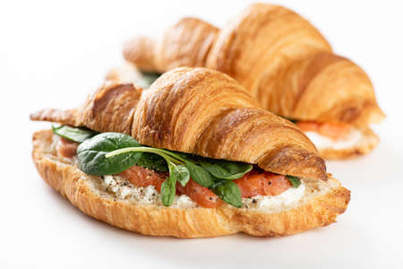french croissant with salmon, cream cheese and spinach on a white background, selective focus