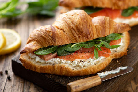 sandwich with salmon, spinach and cream cheese on a wooden board, selective focus, close-up