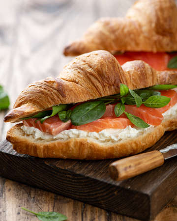 croissant with salmon, spinach and cream cheese on a wooden board, selective focus, close-up