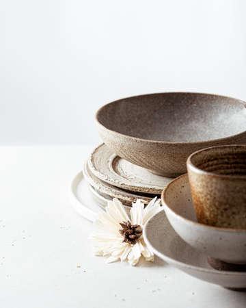 handicraft ceramics, empty craft ceramic bowl, plates and cup on light background Reklamní fotografie