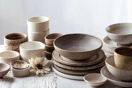 handmade ceramic tableware, empty craft ceramic plates, bowls and cups on light background Reklamní fotografie